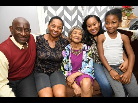 Elsie Smikle is flanked by (from left) son-in-law Collie Petgrave, daughter Diane Petgrave, granddaughter Candice Petgrave and Daiskie Shawat at the Petgraves' home in Stadium Gardens in Kingston yesterday. The Walderston, Manchester, native celebrates h