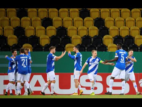 Darmstadt's players cheer after scoring their second goal against Dynamo Dresden during their German Bundesliga second-round match played in an empty stadium, despite more than 72,000 tickets being sold for the game at the Rudolf-Harbig-Stadion in Dresde