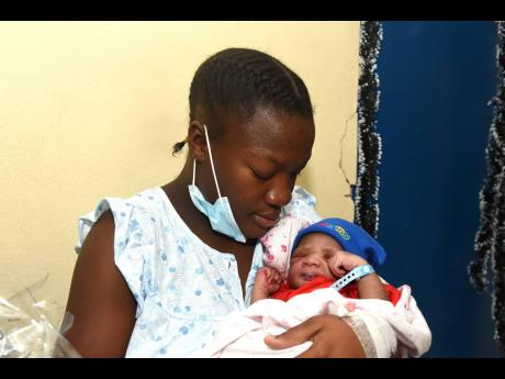 First-time mom Naketa Dockery cradles her newborn Leondre Gray. Leondre was born at 3:34 a.m. on Christmas Day at the Victoria Jubilee Hospital, weighing 3.48kg. The mother received a basket and other supplies from the Kiwanis Club in collaboration with An