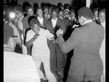 Bunny Grant (left) is all smiles as he spars with Muhammad Ali at the reception given by National Sports Limited at the Jamaica Pegasus Hotel on December 28.