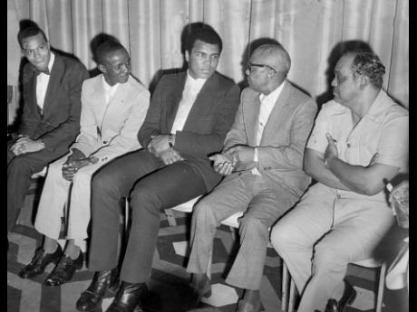 Muhammad Ali (centre) listens intently to Muslim Minister Jam Muhammad (in glasses) in the lobby of The Jamaica Pegasus hotel shortly before the start of reception for him on December 28, 1974. Others in picture from left are Louis Farrakhan, another Musli