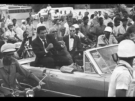"""Muhammad Ali (left) responds to a request from hero-worshipping onlookers to """"show us your fists"""", during the 22-car motorcade from the Norman Manley International Airport on December 28, to The Jamaica Pegasus hotel shortly after the champion and his"""