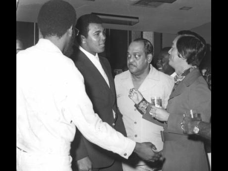 Muhammad Ali (second from left) is all ears as Jamaica's number one boxing promoter and entrepreneur Lucien Chen (right) makes a point after National Sports Public Relations,  Officer Raymond Sharpe (extreme left) had introduced the local sports personal