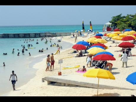Visitors enjoying the Doctor's Cave Beach in Montego Bay, St James. Arrivals and earnings continue to be affected this year by the coronavirus pandemic. A new variant of the coronavirus has dampened optimism for a bounce in the winter tourism season.