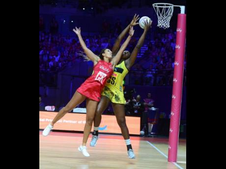 Sunshine Girls captain Jhaniele Fowler (right) outstretches England Roses goal keeper Geva Mentor to claim the ball, before scoring a goal during their Group G Vitality Netball World Cup match in Liverpool, England, on July 15, 2019.