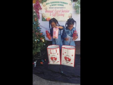 Twins discover their gifts at the annual carol service and gift giving ceremony for children at Bull Savannah Primary and Infant School.