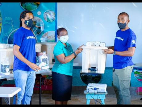 Jennifer Ross (centre), principal, Grace Childcare and Learning Centre, collects her supplies from Travis Graham, executive director, Oracabessa Foundation, while Inilek Wilmot, environmental programmes manager, Oracabessa Foundation, looks on.