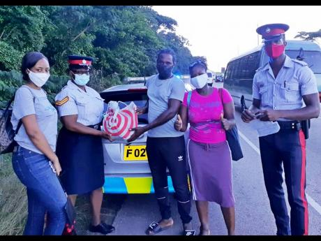 Police officers Leteacher Ennis (second left) and Teran Spence (right), of the St Ann police Community Safety and Security branch, present a gift package to a lucky motorist and his relatives.