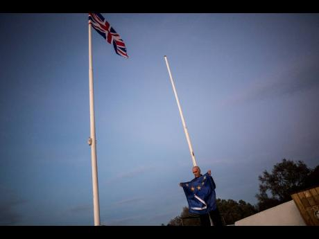 A worker folds the EU flag after it was  lowered at the British territory of Gibraltar.   AP