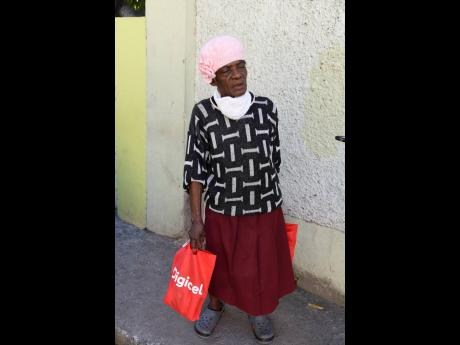 Hellen Harrison stops to speak with The Gleaner as she makes her way home with care packages in August Town, St Andrew, on New Year's Eve.