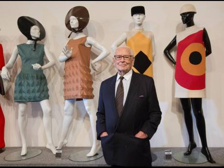 French fashion designer Pierre Cardin poses with dresses behind during the inauguration of the Pierre Cardin Museum in Paris.