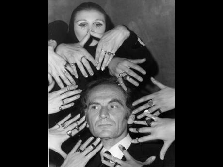 In this September 1969 file photo, French fashion designer Pierre Cardin's face is framed by 10 hands of models like a sculptur of goddess Siva ornamented with a collection of rings designed by Cardin from his latest jewellery collection, in Paris, Franc