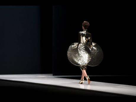 In this March 22, 2016 file photo, a model displays a creation by French fashion designer Pierre Cardin during Moscow Fashion Week, Russia.