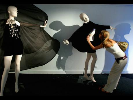 In this July 2006 file photo, a woman looks at a creation by French designer Pierre Cardin as part of his Spring-Summer 2007 fashion collection in Paris.