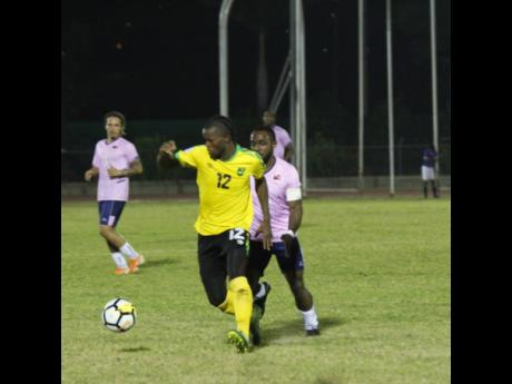 Jamaica forward Kemar Beckford (front) chases after the ball while being harried by Bermuda player Cecoy Robinson during their international friendly match at the Montego Bay Sports Complex on Wednesday, March 11, 2020.