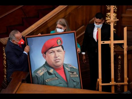 First Lady Cilia Flores (centre) and Socialist party leader Diosdado Cabello (left) carry a portrait of late Venezuelan President Hugo Chávez into the chamber of the National Assembly as the ruling socialist party prepares to assume the leadership of Cong