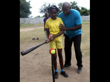 Uel Gordon (right), President of the Jamaica Baseball Association,  demonstrates the proper batting technique to a young participant, during a baseball seminar at Gregory Park Primary School in Portmore, St Catherine in 2014.