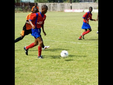 In this Gleaner file photo, a young Romario Mullings (foreground) of Manchester High dribbles past Don-Jay Smith of St Elizabeth Technical during an Under-15 match.