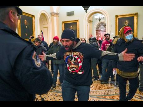 Trump supporters gesture to US Capitol Police in the hallway outside of the Senate chamber after breaching the halls of the Capitol in Washington on Wednesday.