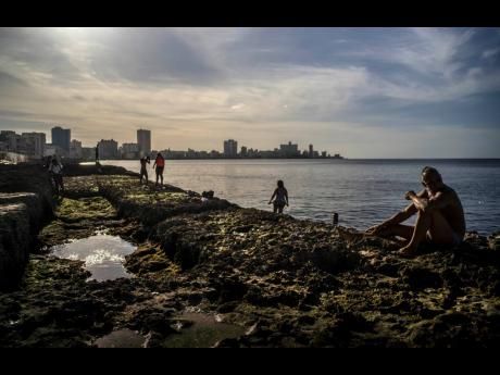 People sunbathing at sunset on the Malecon in Havana, Cuba, on Friday, January 1.