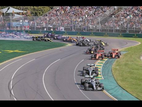 In this March 17, 2019, photo, Mercedes driver Valtteri Bottas (bottom), leads his teammate Lewis Hamilton and the rest of the pack during the start of the Australian Formula 1 Grand Prix in Melbourne, Australia. The start of the 2021 Formula One season ha