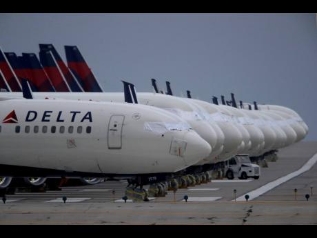 In this May 14, 2020 file photo, several dozen mothballed Delta Air Lines jets are parked on a closed runway at Kansas City International Airport in Missouri.