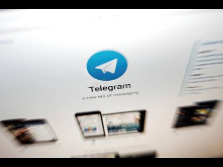 left: The website of the Telegram messaging app is seen on a computer screen.