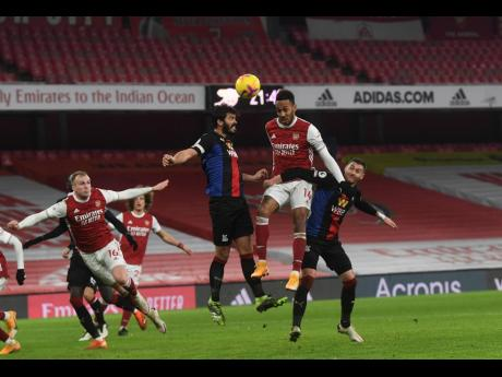 Arsenal's Pierre-Emerick Aubameyang (centre) jumps for the ball during their English Premier League match against Crystal Palace at Emirates Stadium in London, England, yesterday.