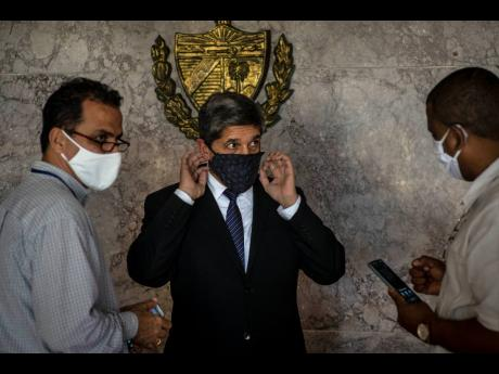 Cuba's Director General of US Affairs Carlos Fernández de Cossio (centre) puts on a mask as a precaution against the spread of the new coronavirus, after a press conference in Havana, Cuba, on January 12, 2021. The Trump administration has re-designated