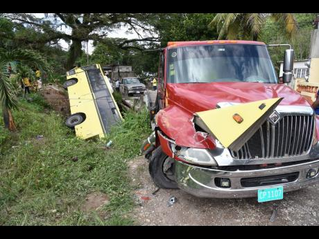 Wreckage from a Jamaica Urban Transit Company bus remains jammed into the bonnet of a parked wrecker in Temple Hall, St Andrew, after the driver reportedly lost control on Thursday. The bus ended up in a ditch.