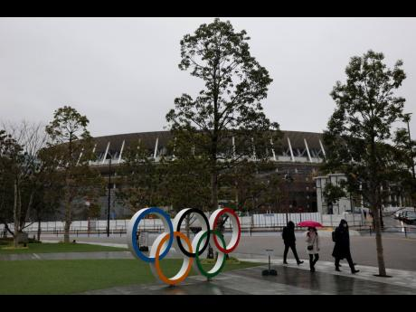 People walk past the Olympic rings near the New National Stadium in Tokyo.