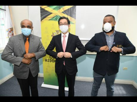 Ambassador Masaya Fujiwara (centre) with Ryan Foster (right), secretary general/CEO, and Christopher Samuda, president of Jamaica Olympic Association (JOA), during a courtesy call at JOA office in September 2020.