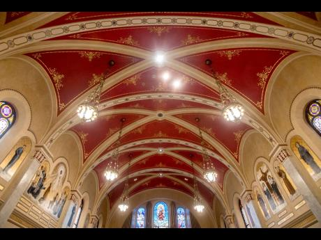 The ceiling of the sanctuary at Sacred Heart Catholic Church is painted red with gold detail work along the edges in Peoria.