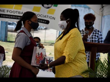 Elaine Walker-Brown, president of St Catherine Football Association, hands over a table to Daina Wright, a female footballer and student of Spanish Town High School, during a tablet donation ceremony at Spanish Town Prison Oval on Friday.