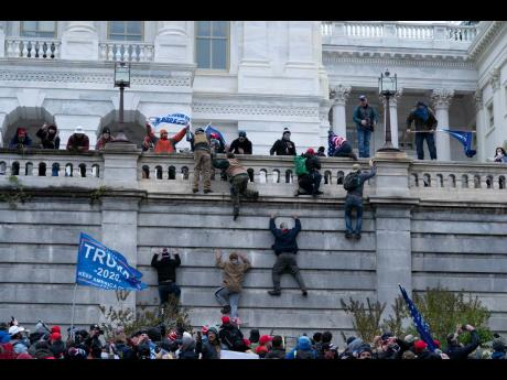 In this January 6, 2021, file photo, supporters of President Donald Trump climb the west wall of the US Capitol in Washington, DC.