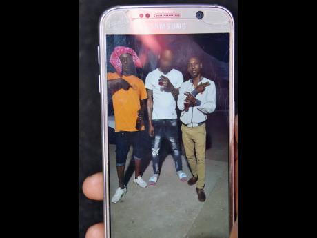 A survivor of the Portmore toll highway crash shows a photo of Jonoi Lewis (right) and another man (left) who perished Sunday morning.