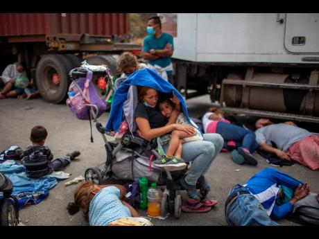 Honduran migrants gather in front of a police roadblock at a highway in Vado Hondo, Guatemala, on Sunday.