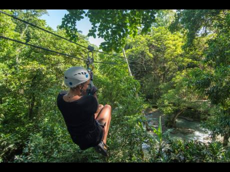 A tourist glides across the Chukka 'Falls Flyer' zip line located at Dunn's River Falls. The Falls Flyer zip line is one of three activities being promoted by the Urban Development Corporation via its 'Triple Thrills' promotion.