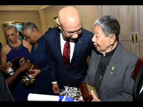 Governor General Sir Patrick Allen (left) speaks with awardee Reverend Easton Lee at the National Chorale of Jamaica Medal of Excellence Awards ceremony at King's House in St Andrew on May 5, 2019.