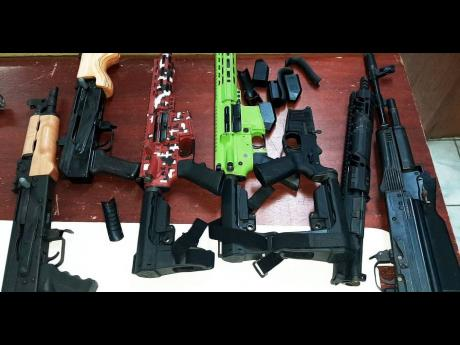 Guns and ammunition were discovered in a fridge at a Montego Bay wharf on Monday, January 18. This photo shows assault rifles that were among 19 illegal guns found at another wharf in MoBay last week.