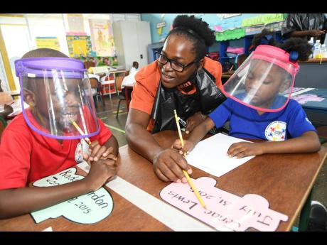 Teacher Taneka McKoy-Phipps, who gained popularity for her walkabout blackboard campaign, explains a concept to Kador Gordon (left) while Jenae Lewis listens attentively at Union Gardens Infant School in Kingston 13 on Tuesday. Business mogul and philanthr