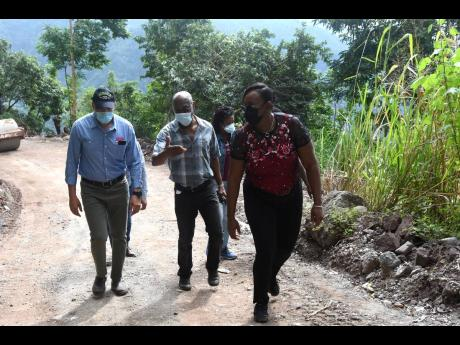 National Works Agency CEO E.G. Hunter (centre) touring the Gordon Town and Savage Pen roads alongside Prime Minister Andrew Holness and St Andrew East Rural Member of Parliament Juliet Holness on December 5. The Government allocated Christmas funding to re