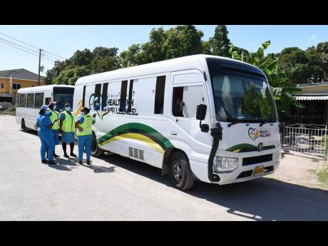 Ministry of Health staff congregate outside a coronavirus mobile unit in Washington Gardens, St Andrew, on Thursday.