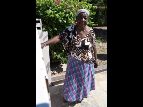 Delletha Adams stands by her gate in Washington Gardens, St Andrew, shortly after undergoing a COVID-19 test at a Ministry of Health mobile unit on Thursday.