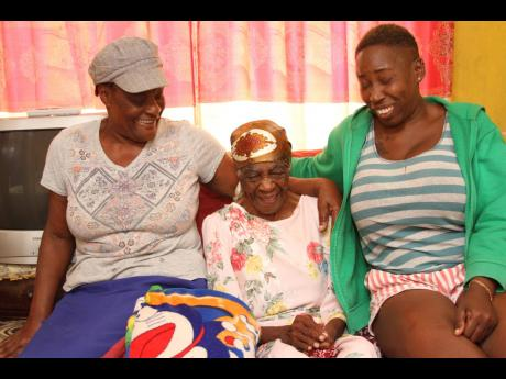 Centenarian Roslyn Stephens of Spaldings, Clarendon, shares a light moment with her daughter-in-law Yvonne Knight (left) and her caregiver and granddaughter Tracy Stephens (right). Roslyn, who was a farmer and minister of the gospel, is giving God thanks f