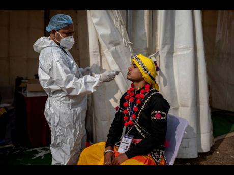 A health worker takes a swab sample of a folk artists to test for COVID-19 during a press preview of the upcoming Republic Day parade, in New Delhi, India, Friday, January 22, 2021.