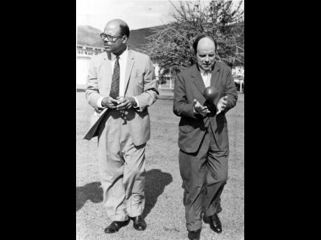 In this June 1960 photograph, Sir Dr Arthur Lewis (left) walks with Main Macleod, secretary of state for the Colonies, who is seen playing with a calabash which had been picked from the tree in the background.