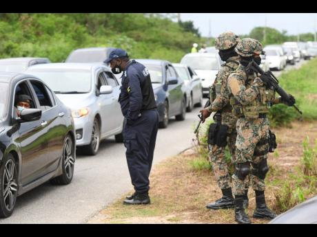 Members of the security forces carrying out an operation along the Hellshire main road last October, taking into custody a number of persons who could not produce identification or give a suitable reason for being in the area. Earlier in the day, they had
