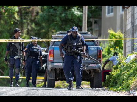 Police officers at a crime scene in Goldsmith Villa, located in August Town, St Andrew, where one person was shot dead and another two injured in 2019.