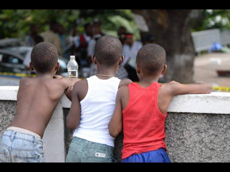 File  These youngsters try to get a glimpse of the crime scene at Crystal Towers apartment complex in St Andrew, where the body of a woman was discovered on December 10, 2016. Dr Herbert Gayle noted that women were also victims of crime, with more than 90